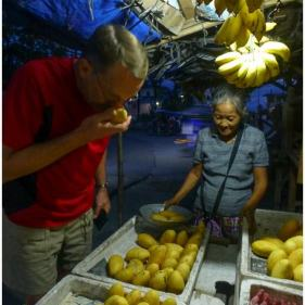 """Sniffing"" mangoes at a produce stand"