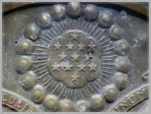 State seal riddled with shrapnel and holes
